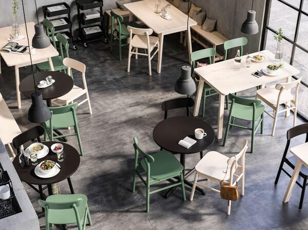 Pyöreitä ja neliskanttisia pöytiä kahvilatilassa. Kaikkien pöytien ympärillä RÖNINGE-tuolit. Suuret HEKTAR-valaisimet roikkuvat katosta.