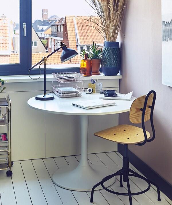 Pyörivä tuoli, pyöreä pöytä ja työvalaisin.