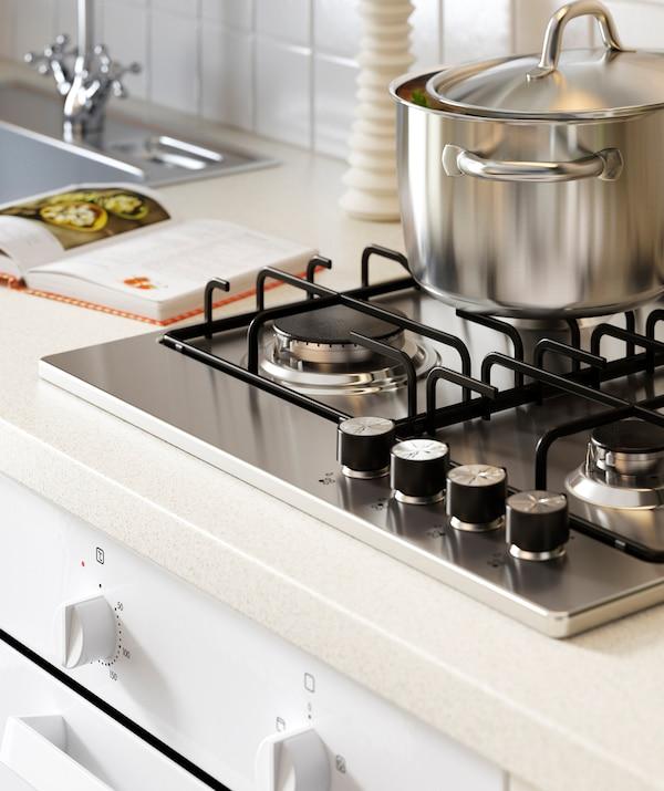 قدر فضي على موقد على سطح مطبخ أبيض بجوار حوض معدن.