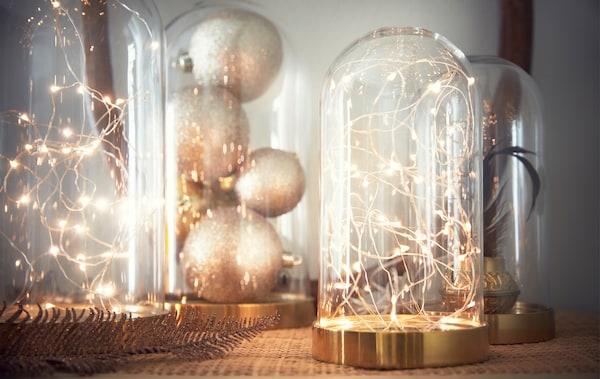 قم بترتيب سلسلة إضاءة رقيقة تعمل بالبطارية داخل قبة زجاجية تزيينية.