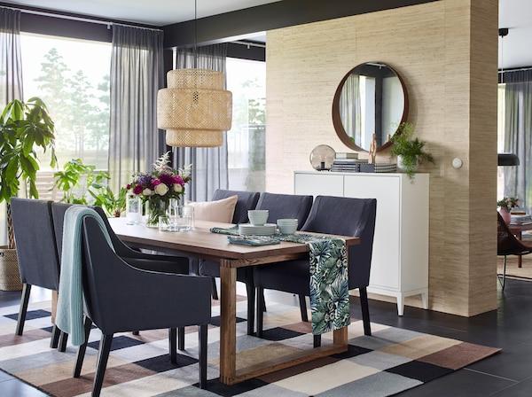 قماش TORGET مزخرف برسومات نباتات يُستخدم كمفرش طاولة في غرفة الطعام مع مصباح سقفي SINNERLIG منسوج فوق طاولة الطعام.