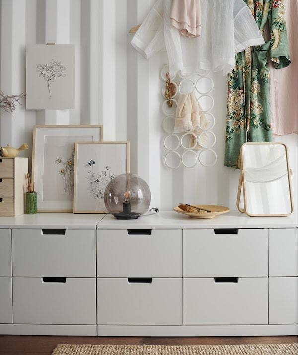 Quadri, una lampada e uno specchio sul ripiano di una cassettiera bianca bassa e vestiti appesi a una parete bianca – IKEA