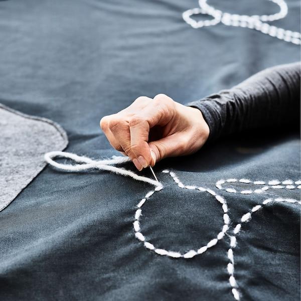 Qualcuno ricama la forma di un piatto su una tovaglia; un tavolo da giardino coperto con una tovaglia da usare anche come tappeto da gioco - IKEA.