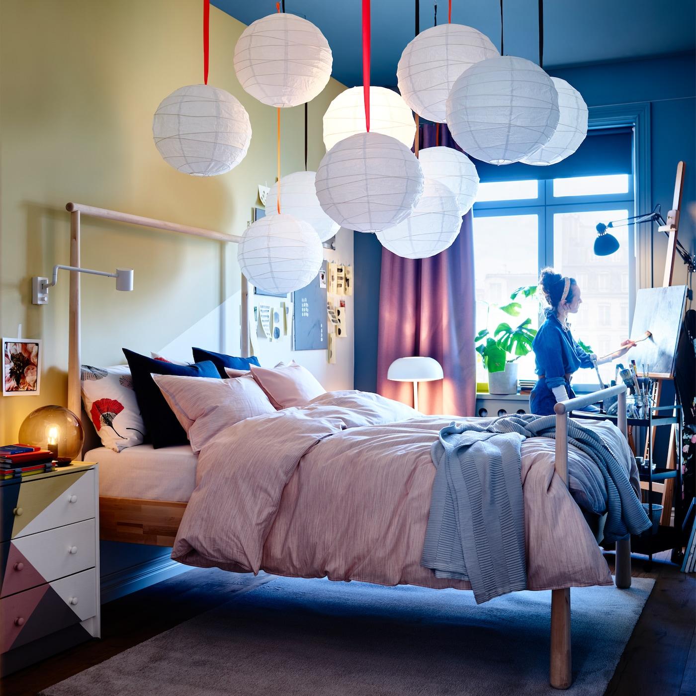 Quarto com estrutura de cama GJÖRA em bétula, candeeiros suspensos em branco, têxteis de cama em rosa, um candeeiro de mesa cinza e cortinados lilás.