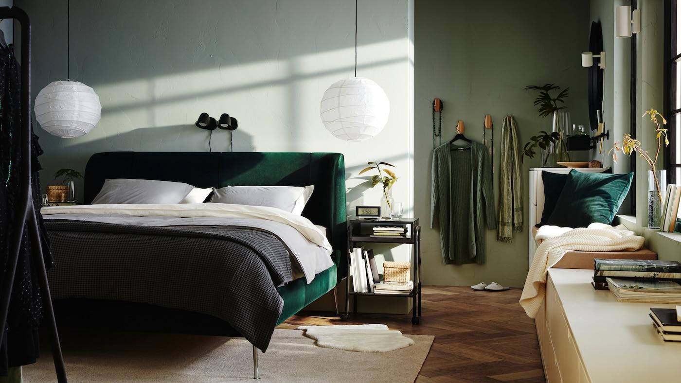 Quarto com uma cama TUFJORD em verde com abajures REGOLIT por cima e blocos de gavetas NORDLI com livros perto das janelas.