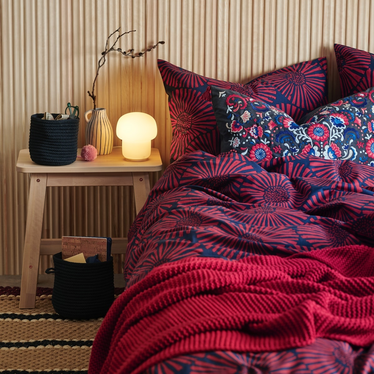 Quarto em madeiras claras com roupa de cama vermelha e azul da estação.