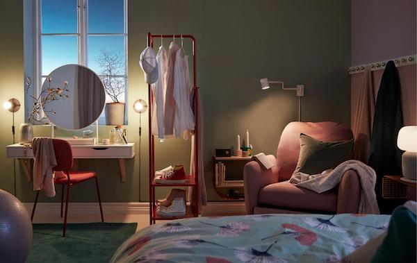 Quarto iluminado com luz suave, com toucador, suporte para cabides a dividir o espaço e um canto de leitura com poltrona reclinável.