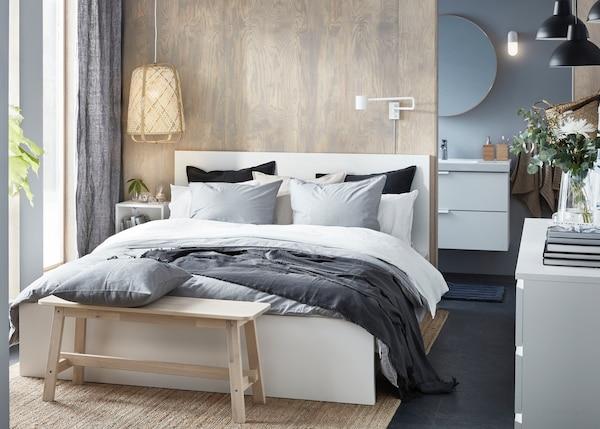 Quarto ilumincado com uma cama MALM branca e roupa de cama em tons de cinza