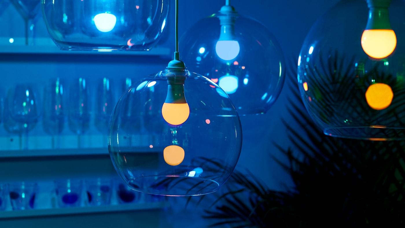 Quatre abat-jour JAKOBSBYN en verre placés à différentes hauteurs, avec des ampoules LED TRÅDFRI à variation d'intensité, dans une pièce faiblement éclairée.