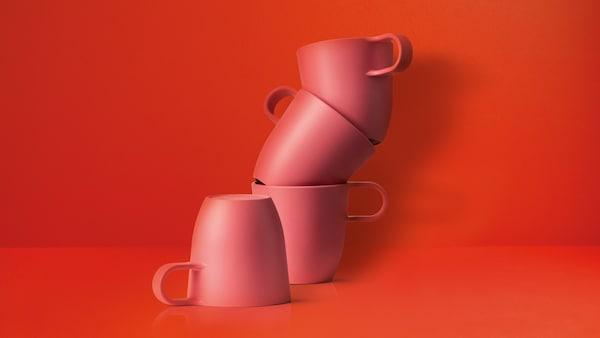 Quatre mugs rouges empilés sur fond rouge