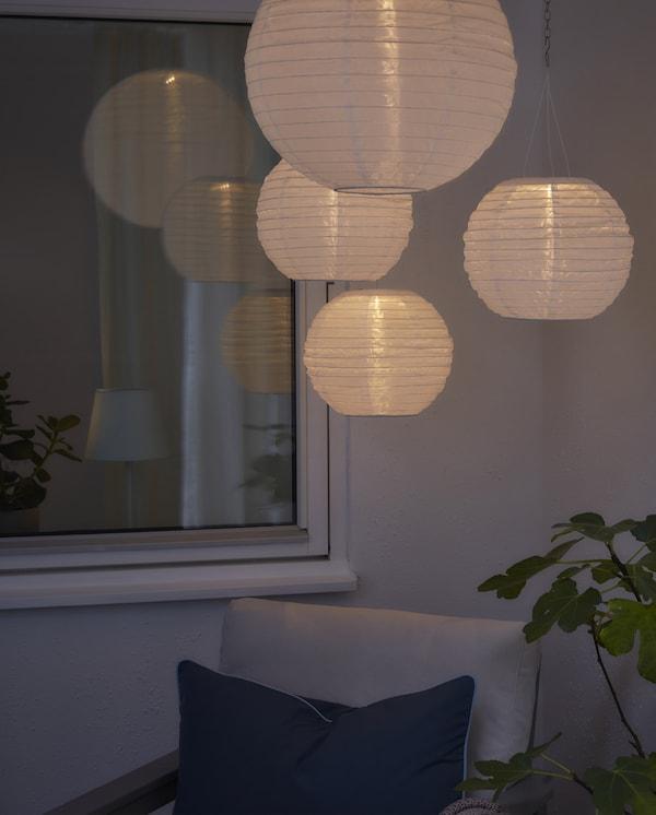Quatre suspensions rondes à énergie solaire donnent un agréable éclairage d'ambiance dans un espace extérieur plongé dans la pénombre.