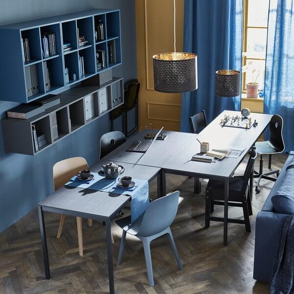 Quatre tables placées en zigzag permettant des activités diverses: heure du thé, jeux et travaux scolaires