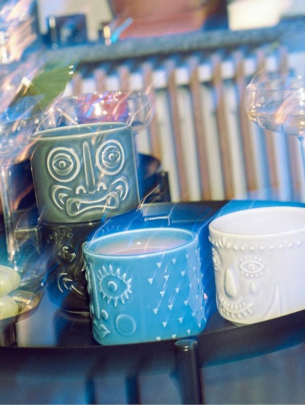 Quattro bicchieri della collezione FREKVENS di vari colori su un tavolo nero - IKEA
