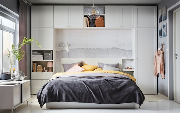 Queen size white MALM ottoman bed with gray and yellow bedding, surrounded by white PAX closet system