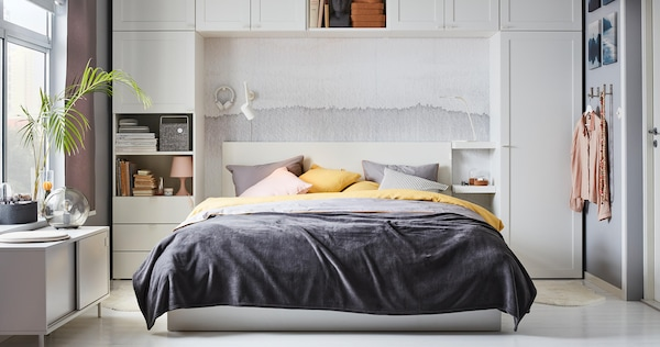 Queen size white MALM ottoman bed with gray and yellow bedding, surrounded by white closet system