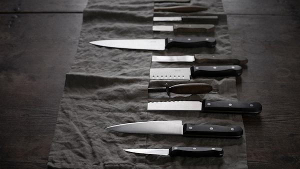 Quelques couteaux de cuisine VARDAGEN de tailles variées disposés sur une trousse à couteaux gris foncé.