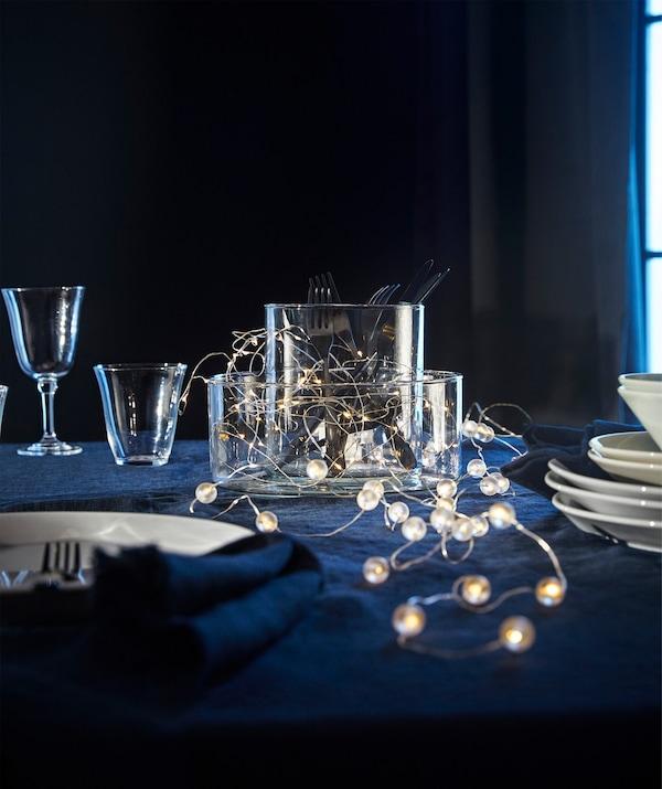 Quelques guirlandes lumineuses à LED IKEA SNÖYRA déposées sur une table garnie de verres, de vases et d'assiettes.