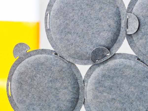 Quelques panneaux acoustiques ronds ODDLAUG en feutre gris, attachés ensemble afin d'absorber les bruits agaçants.