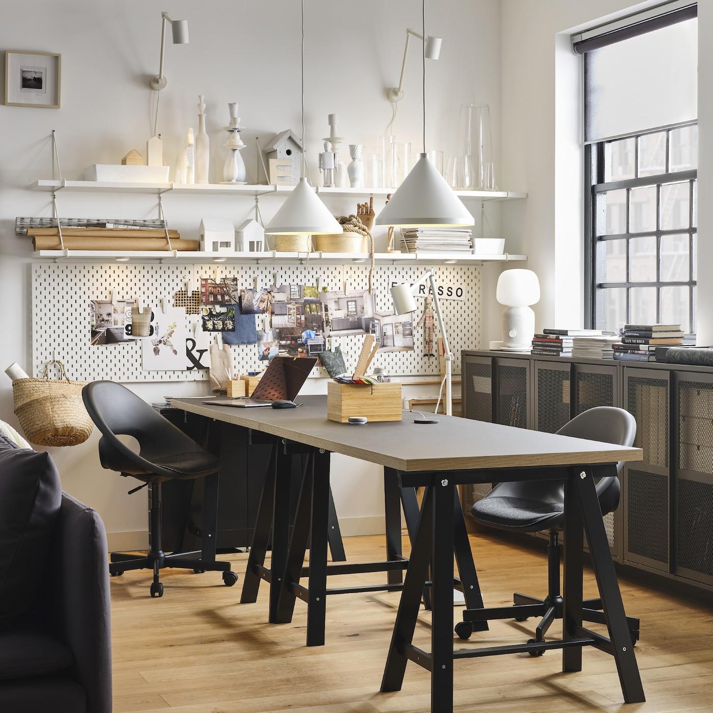 Рабочее место с двумя черными письменными столами и двумя рабочими стульями, два белых подвесных светильника и белые настенные полки.