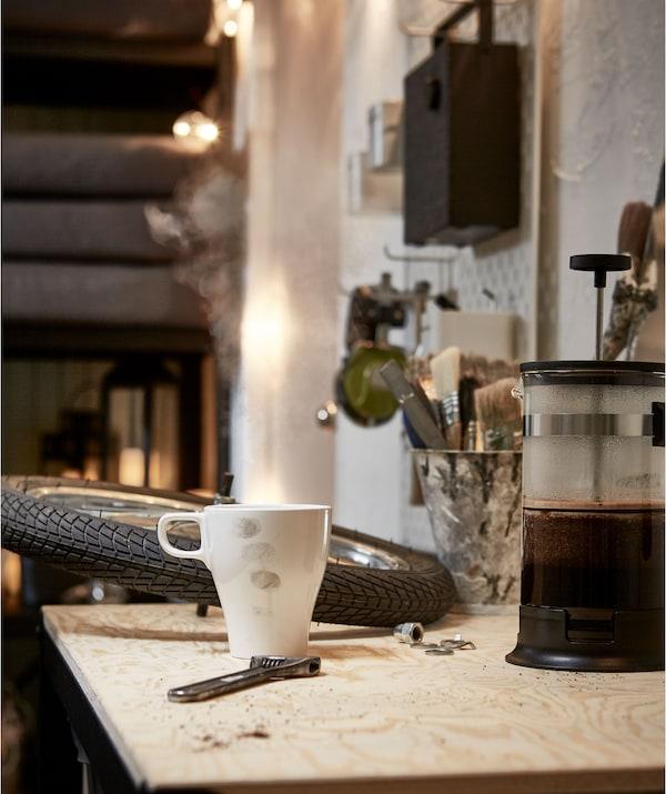 Radna površina u sobi nalik garaži, kotač bicikla i francuski ključ na površini s kuhalom za kavu i lagano obojenom šalicom.