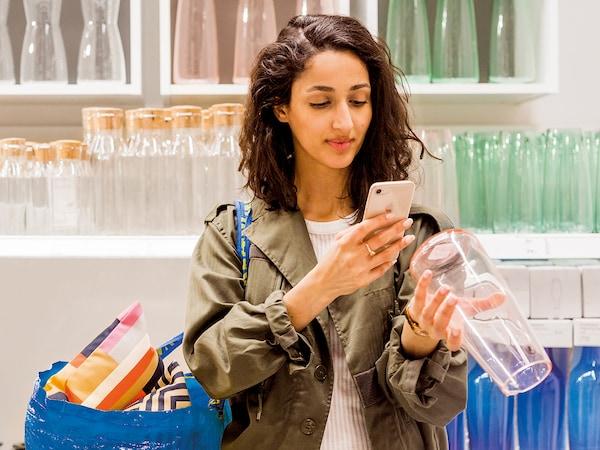 Ragazza che scansiona con il proprio cellulare il codice a barre di un prodotto IKEA
