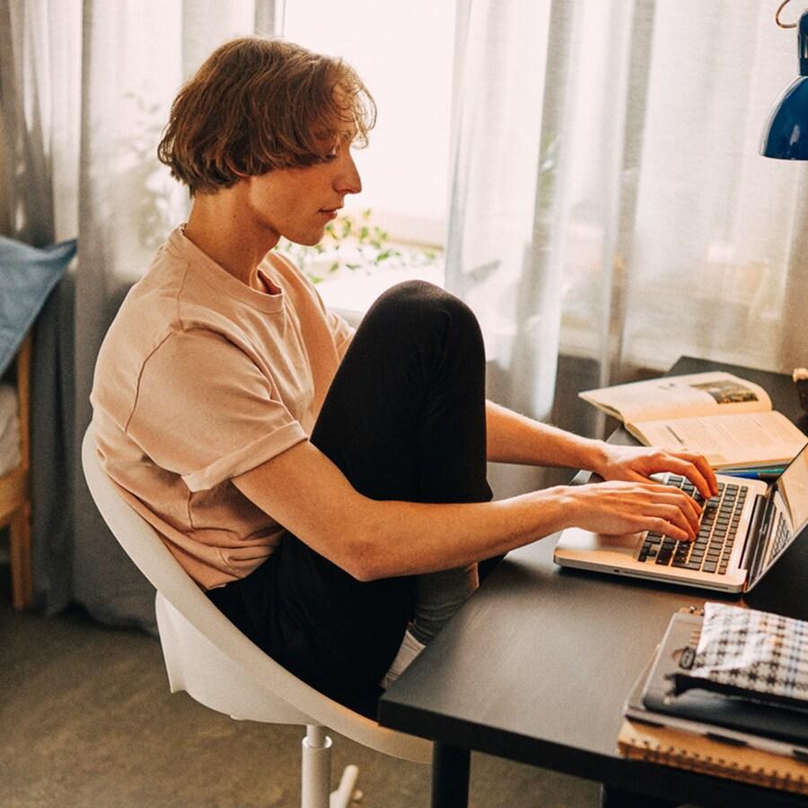 Ragazzo che scrive al computer seduto  alla scrivania - IKEA