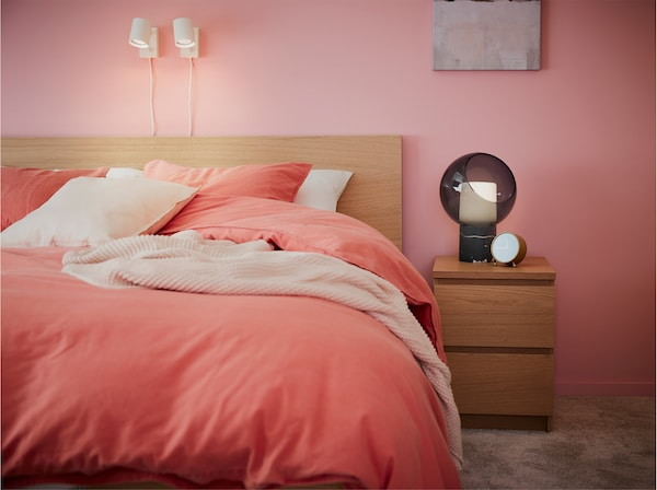 Rama łóżka i stolik z bejcowanego na biało dębu, jasno brązowo-czerwone tekstylia na łóżko i białe lampy.