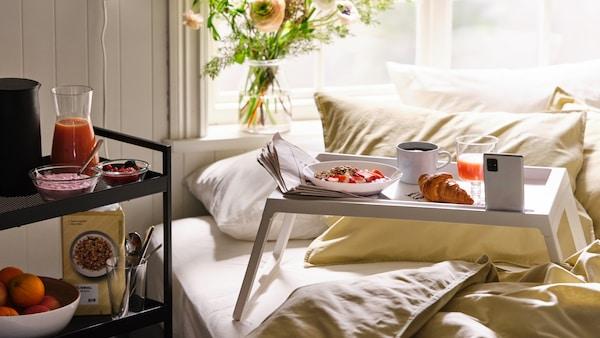 Raňajky naservírované na podnose do postele KLIPSK, na posteli obliečky ÄNGSLILJA, na vozíku vedľa postele ďalšie jedlo.