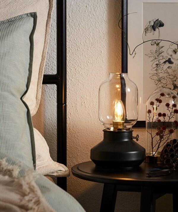 Rand eines Bettes mit hohem Kopfteil, u. a. mit einer TÄRNABY Tischleuchte, die in der Form an eine alte Kerosinleuchte erinnert.