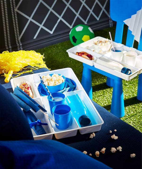 Range-couverts servant de plateau restauration pour les supporters, avec compartiments pour boissons, snacks et fanions.