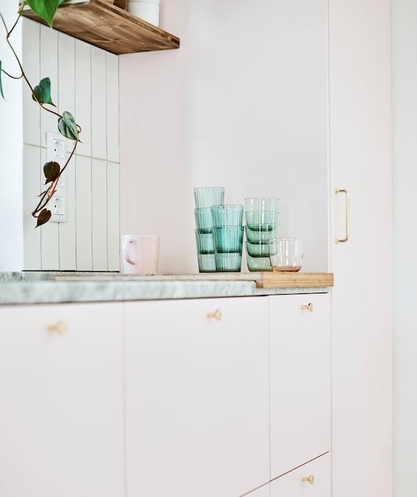 Rangée d'unités de cuisine à portes roses avec une pile de verres verts et une tasse rose sur une planche à découper sur le comptoir en marbre.