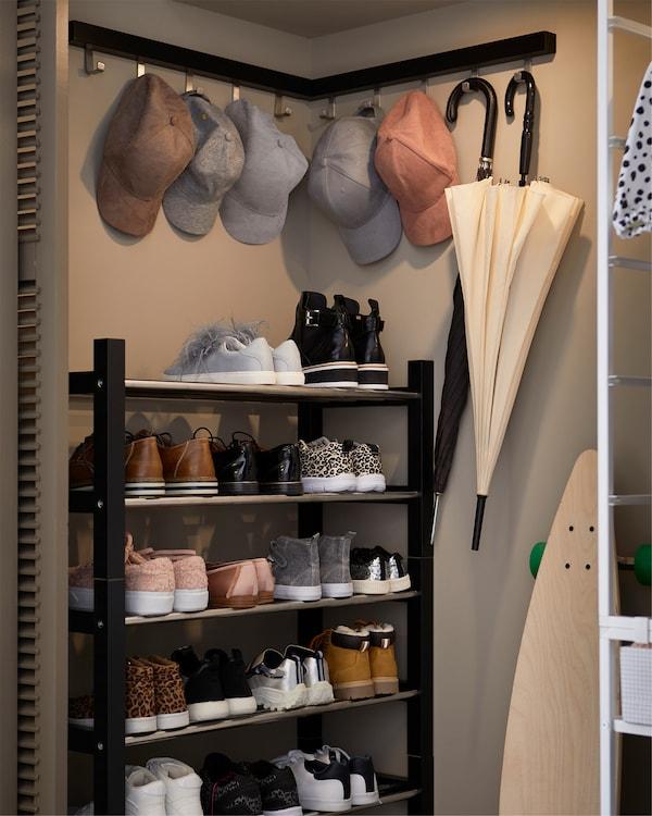 Rangement d'angle intégré, équipé sur toute sa hauteur d'étagère à chaussures en noir et acier inoxydable.