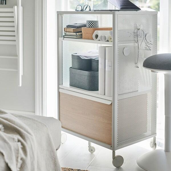 Rangement en filet blanc à roulettes contre une fenêtre.