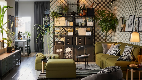 Rangement modulaire IKEABROR noir avec des boîtes et des range-tout posés sur ses trois tablettes, et des armoires à portes noires dans un salon.