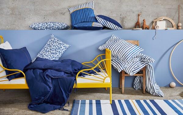 Rangka katil kuning dengan peralatan tidur biru putih bercorak bunga dan bercetak jalur, dan kusyen dan mainan kayu di atas dinding biru.