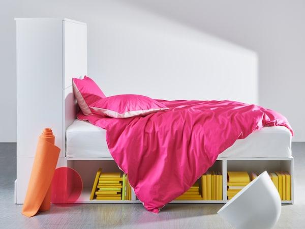 Rangka katil putih PLATSA dengan storan menunjukkan para terbuka di bawah katil dan storan tertutup dengan pintu di satu bahagian.
