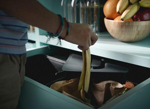 Rapaz com pulseiras, a colocar uma casca de banana no sistema de reciclagem VARIERA.