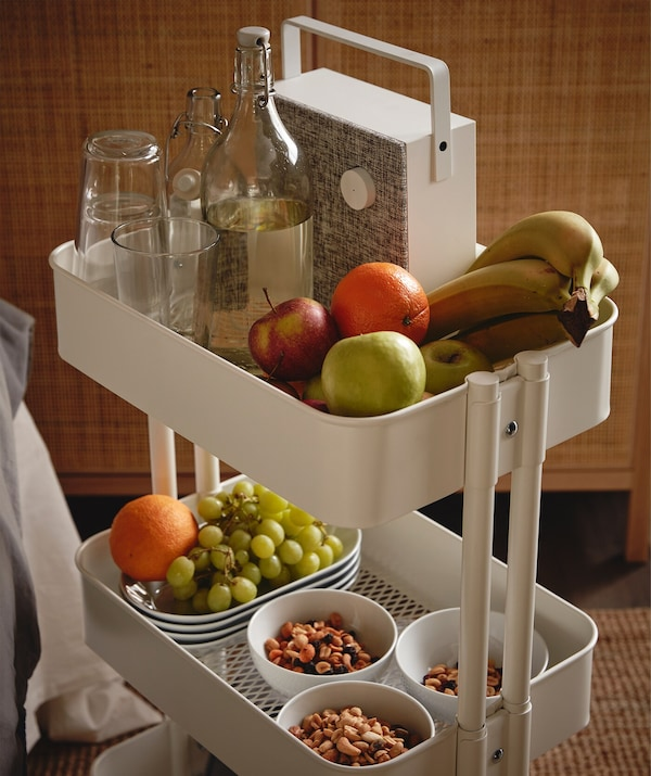 RÅSKOG trolley filled with various snacks and fruits, a KORKEN bottle and drinking glasses, and an ENEBY Bluetooth speaker.