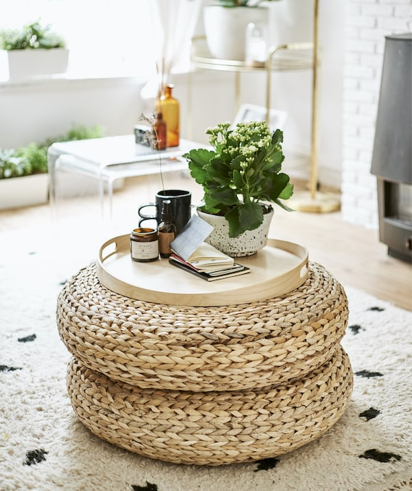 Rattan footstools stacked and used as a side table.