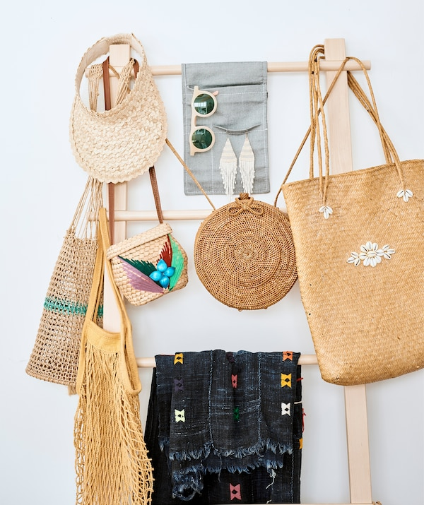 Rattan handbags and accessories hanging on a wooden ladder stand.