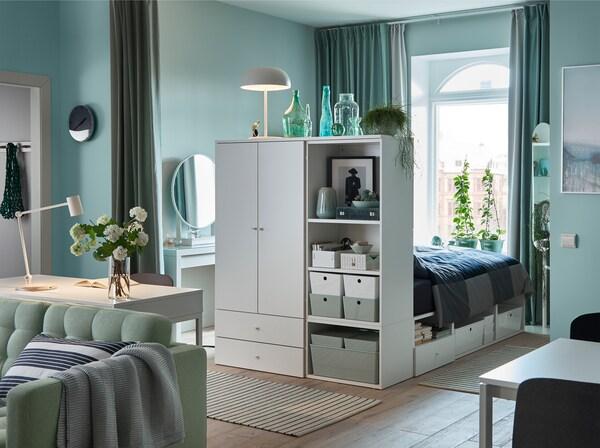 Rauhallinen ja vaaleanvihreä yhden makuuhuoneen huoneisto, jossa on vihreät verhot, vihreä sohva ja valkoinen sängyn runko, jossa säilytystila.
