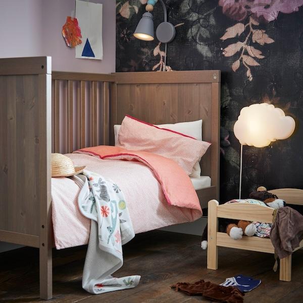 Rauhoittava lastenhuoneen sisustus. IKEA DRÖMSYN pilvilamppu antaa mukavan hämyistä iltavaloa. IKEA SUNDVIK pinnasänky, jossa on irrotettava laita, kasvaa lapsen mukana. IKEA LANTLIG seinävalaisin on koristeltu puuhelmillä.