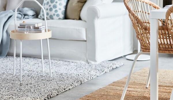 Raum mit einem weissen Sofa und verschiedenen Kissen, sowie einem VINDOM Hochflorteppich und LOHALS Flachgewebeteppich auf dem Boden.