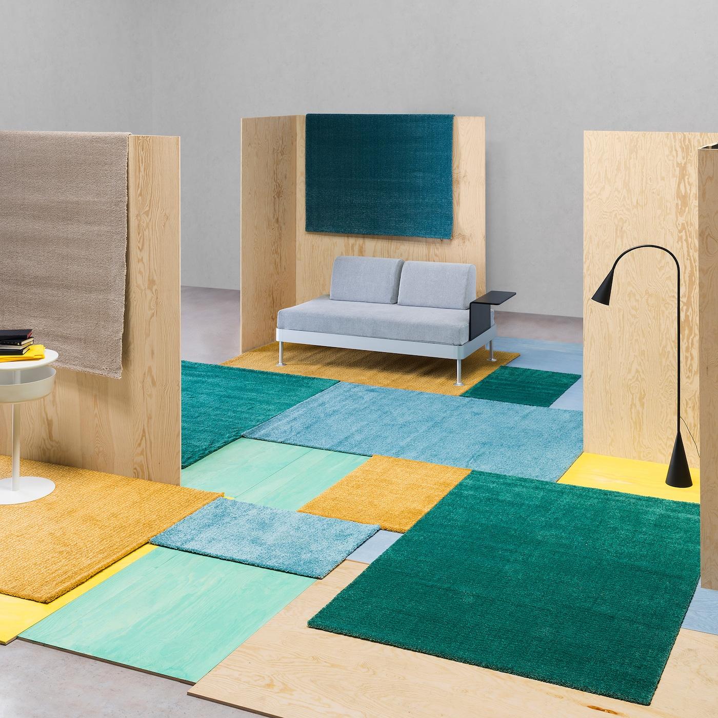 Raum mit Raumtrennern aus Holz, einem Sofa & verschieden farbigen Teppichen in grün, gelb & blau.