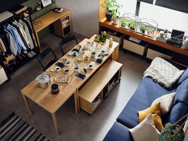 RÅVAROR Esstische und Aufbewahrungselemente sind zu einem Essbereich zusammengestellt. Auf den Tischen stehen Geschirr, Gläser und Töpfe und Schüsseln mit Essen.