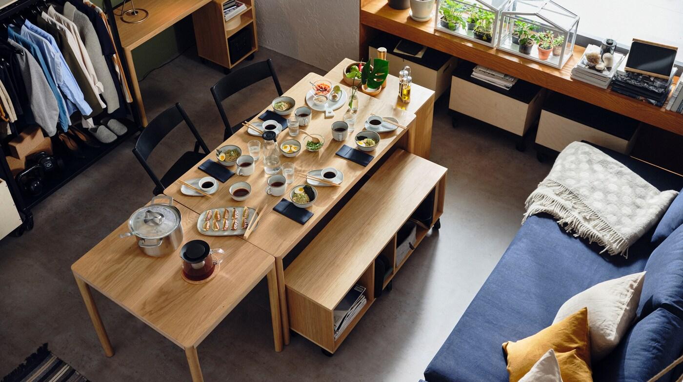 RÅVAROR tafels en opbergeenheden zijn gecombineerd tot een eetruimte. Op de tafels staat servies met eten.
