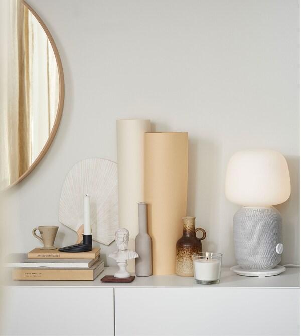 Razni ukrasi u zemljanim bojama na beloj površini, uključujući sivu i belu SYMFONISK stonu lampu.