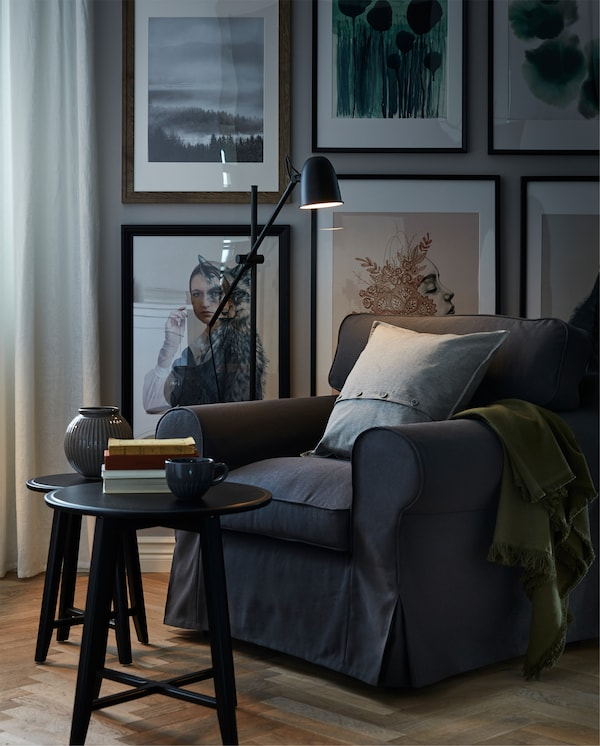 Reading nook with a big, soft armchair, reading light, books on a coffee table and the wall behind covered in art.