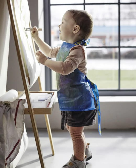 Ребенок рисует в фартуке из синей сумки ИКЕА