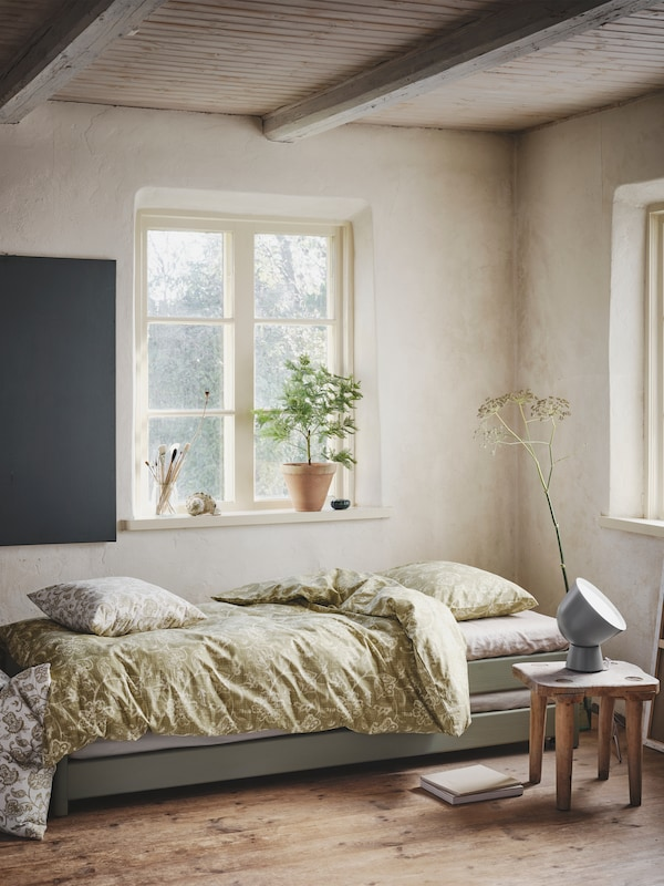 Recanto dun cuarto ben iluminado con teito de madeira e un cómodo canapé cun conxunto de cama JUNIMAGNOLIA verde oliva.